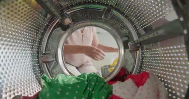 Hausfrau zieht bunte Wäsche aus Waschmaschine