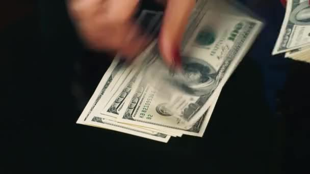 Hands spread banknotes of hundred dollars on the table
