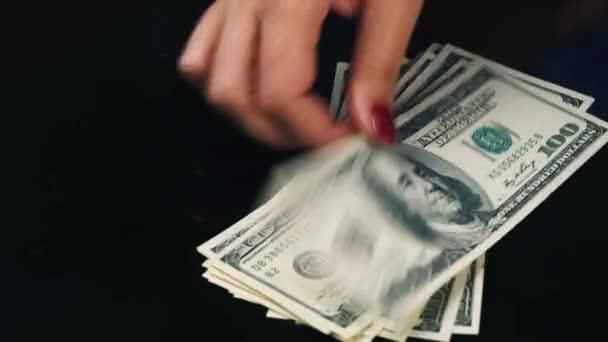 Ruce šíří bankovky sto dolarů na stůl