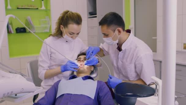 Zahnarzt und seine Assistentin untersuchen ein Patienten