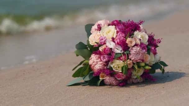 Svatební kytice ležící na písku