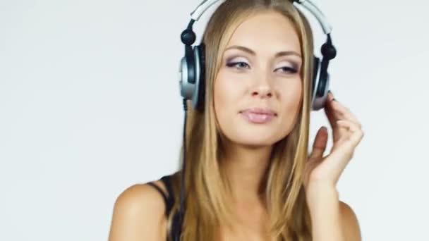 Blonde in headphones smiles flirting