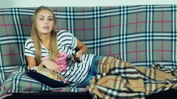 Atraktivní žena ležet na gauči a sledování televize
