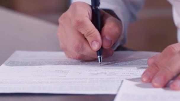 Mann schreibt Text von Hand in Dokumente