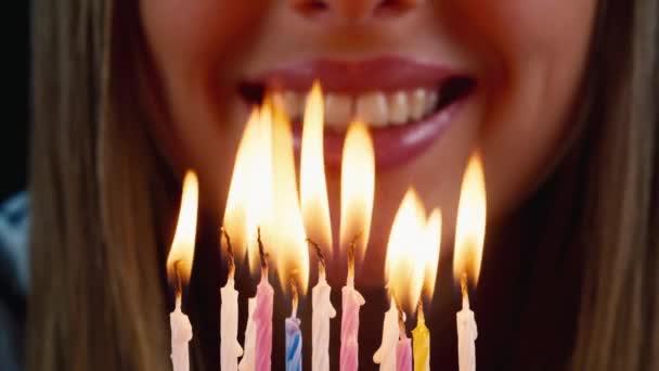 Lány fúj a gyertyákat a tortán, mosolyog
