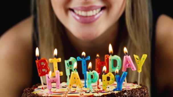 Mädchen bläst die Kerzen auf dem Kuchen aus, lächelt