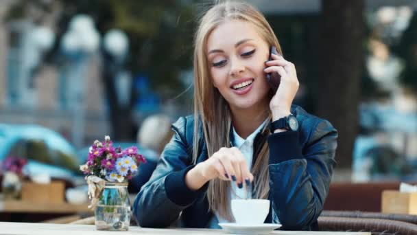 Attractive girl sitting in cafe and talking on cell phone