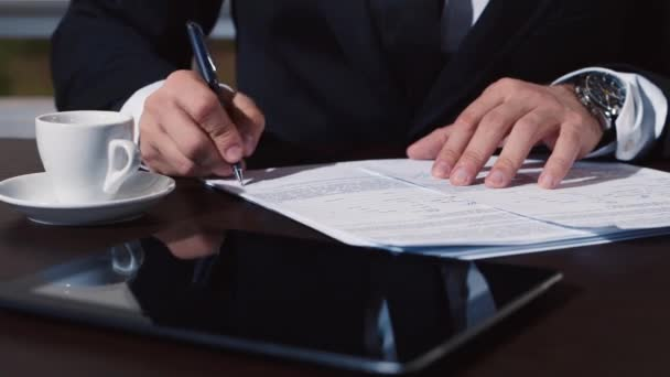 Mans hand in a business suit signs documents