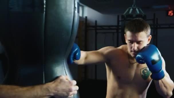 Sportlichen Mann Boxen. Strong trifft der Boxsack