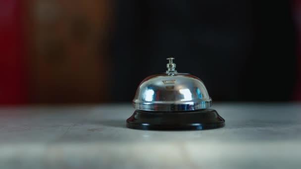 Hand, schlägt die Glocke an der Hotelrezeption
