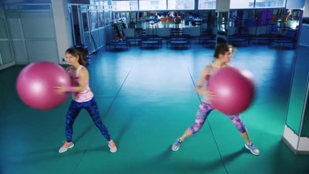 zwei Frauen machen Übungen mit Bällen