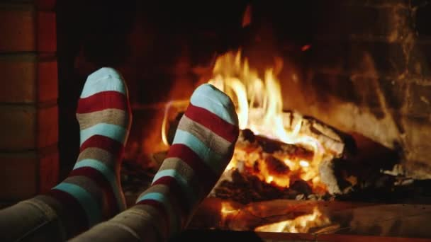 Legs in socks on the background of a burning fireplace