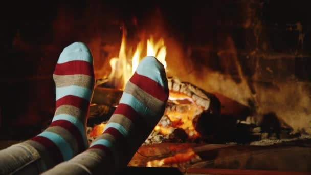 The girl warms his feet by the fireplace