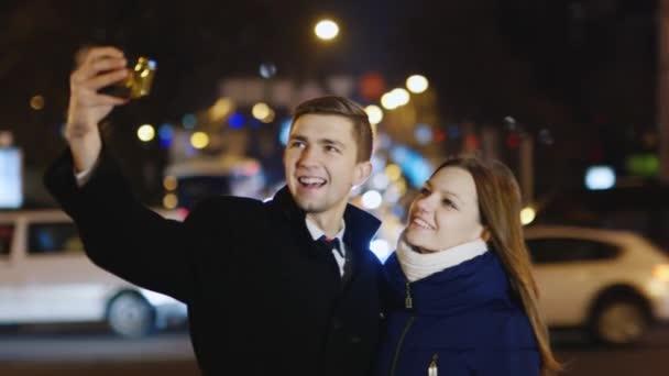 junges Paar fotografiert sich selbst vor dem Hintergrund der Stadt bei Nacht