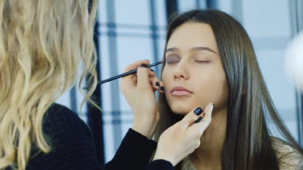 A young girl apply makeup