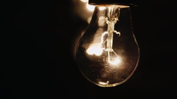 Žárovka svítí jasně na černém pozadí