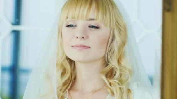 Junge attraktive Braut sieht in den Spiegel. Sie hat blonde Haare und blaue Augen
