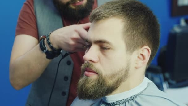Male barber at work, doing hairstyle young man