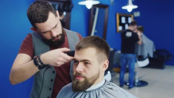 Barbiere taglia i capelli del cliente con clipper