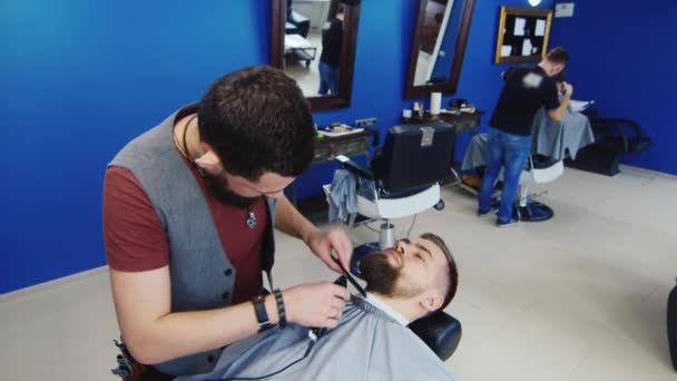 Mens hairstyling and haircutting in a barber shop or hair salon. Grooming the beard. Barbershop. Man hairdresser doing haircut beard adult men in the mens hair salon. Hairdressers in the workplace