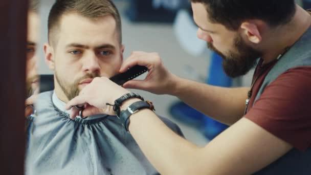 Pánské kadeřnictví a haircutting barber shop nebo vlasy salon. Zastřihování vousů. Holičství. Muž kadeřník dělá střih vousů dospělých mužů v kadeřnictví Pánské. Kadeřnictví na pracovišti
