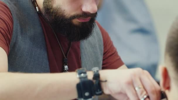 Mens hairstyling and haircutting in a barber shop or hair salon. Grooming the beard