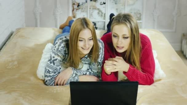 zwei junge sexy Mädchen kommunizieren mit Laptop