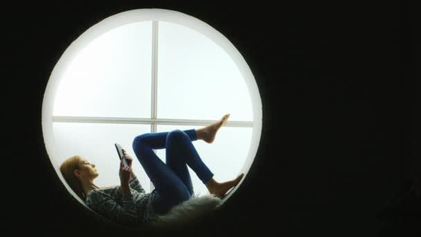 Silhouette eines Mädchens mit dem Tablet auf dem runden Fenster