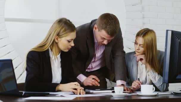 Podnikatel a dvě ženy, které pracují s tabletem