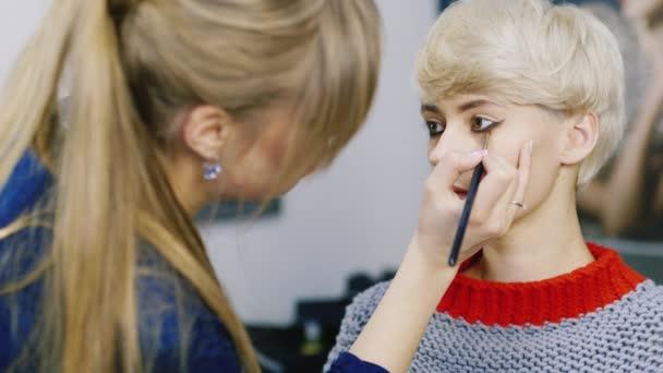 Une jolie femme avec une coupe courte appliqué maquillage u vidéo