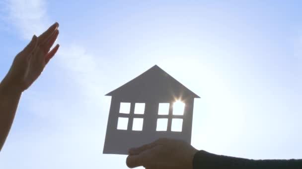Grundriss eines Papierhauses auf blauem Himmelshintergrund. Ein Mann und eine Frau legten ihre Hand auf das Haus. Das Konzept der Familie, Immobilientransaktionen.