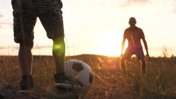 Egy apa és fia játszik egy mezőn egy focilabdával. Egy boldog család sziluettje naplementekor..