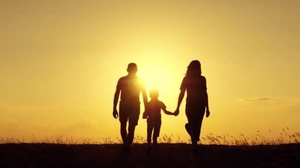 Vater und Mutter halten ihre kleinen Söhne an den Händen. Die Familie läuft dem Sonnenuntergang entgegen. Glückliche Familie. Einigkeit und Unterstützung