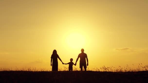Vater und Mutter halten Händchen mit ihrem kleinen Sohn. Die Familie geht bei Sonnenuntergang spazieren. Glückliche Familie. Einigkeit und Unterstützung