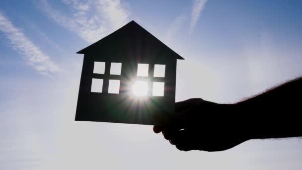 Silhouette eines Papierhauses vor blauem Himmel. Hand in Hand ein Modell eines Papierhauses. Wohnungsbau, Miete, Hypothek.