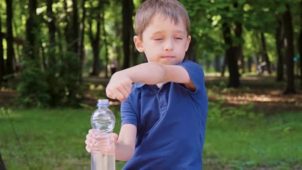 glückliches Kind, das sich im Park ausruht. Das Kind trinkt Wasser aus einer Flasche. Das Konzept der gesunden Entwicklung von Kindern und die Versorgung mit sauberem Trinkwasser.