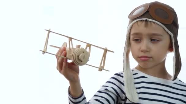 Glücklicher Junge, der im Flugzeug auf weißem Hintergrund spielt. Porträt eines Kindes Spaß Familie Traum Freiheit Flugzeugkonzept. Reisen und Tourismus.