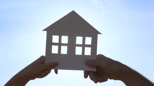 Hände eines Mannes und einer Frau, die ein Haus aus Papier gegen den blauen Himmel halten. Eine junge glückliche Familie träumt von einem eigenen Haus. Das Konzept des Mietwohnungsbaus und der Hypothekenfinanzierung.