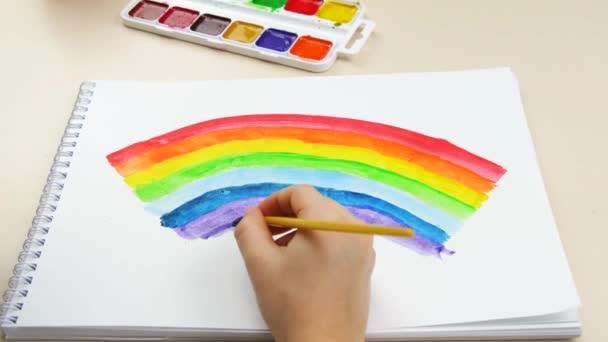 Dětská ruka kreslí duhu s jasnými barvami v detailu. Uzamčení. Společenská vzdálenost během pandemie