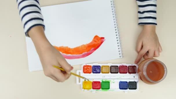 A gyerekek rajzolnak. Egy gyerek szivárványt rajzol. Gyermek festészet szivárvány, a remény jele a koronavírus kitörésekor.
