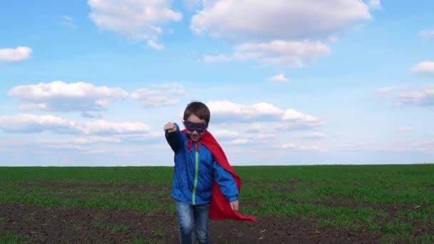 Šťastný chlapec v červeném plášti běží přes louku proti modré obloze. Dítě zobrazuje kreslený styl. Vtipná kreslená postava superhrdiny. Koncept vedení.