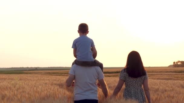 Ein Familienspaziergang durch ein Weizenfeld bei Sonnenuntergang. Ein Vater hält seinen Sohn. Die Familie hält Händchen. Vater und Kind. Mutter und Kind. Die Silhouette einer Familie.