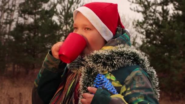 Na Štědrý večer, chlapec pije z červeného poháru na ulici.