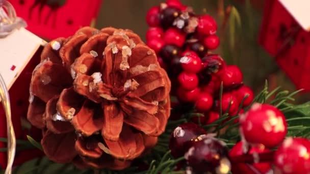 Karácsony este fenyőtoboz és vörös gyöngyök lógnak a fán..