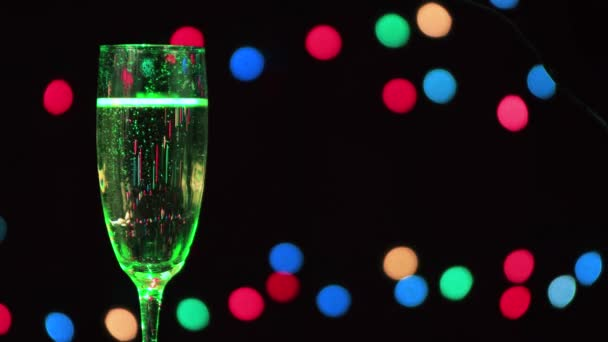 Ein Glas Weihnachts-Champagner mit einem grünen Strahl, der sich entlang bewegt.