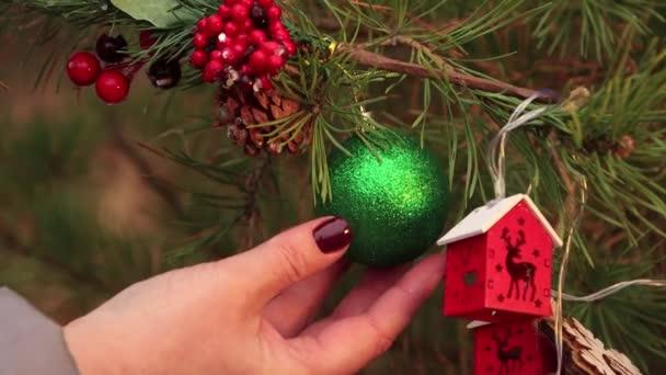 Karácsony este a női kezek zöld labdával díszítik a fát..