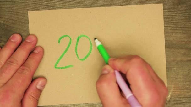 A férfi kézzel ír egy zöld markerrel 202, majd piros 1-et ad hozzá..