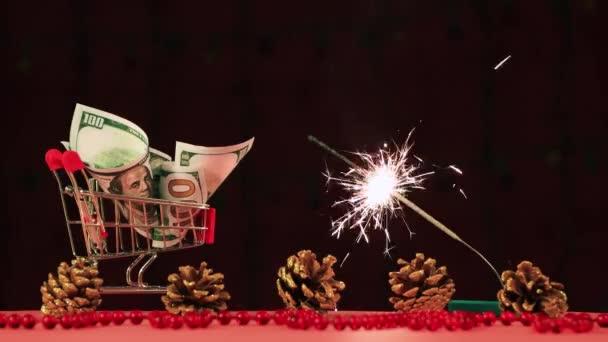 Karácsonyra, pénz egy kosárban és egy égő csillagszóró..