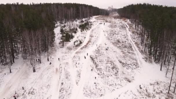 Erwachsene und Kinder fahren mit einem aufblasbaren Schlitten den Berg hinauf und hinunter.