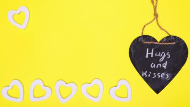 Černé srdce s nápisem se pohybuje na žlutém povrchu.
